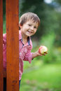 Adorable boy, holding apple, standing next to a door Royalty Free Stock Photo