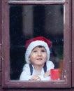 Adorable boy looking through window waiting for santa Stock Photography