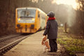 Adorable boy on a railway station waiting for the train with suitcase and teddy bear Royalty Free Stock Photo