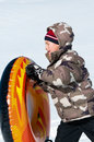 Adorable boy walking with tube in the snow cute tobaggan and camo coat Stock Photo