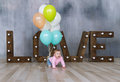 Adorable caucasian baby girl with colorfull balloons creeps on wooden floor at studio Royalty Free Stock Photo