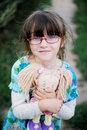 Adorable child girl in glasses hugs baby doll Royalty Free Stock Photo