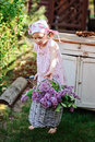 Adorable child girl in pink plaid dress near vintage bureau with lilacs in basket spring garden Stock Image