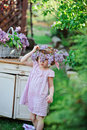 Adorable child girl wearing lilac wreath in pink plaid dress near vintage bureau in spring garden Royalty Free Stock Photo
