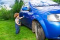 Adorable child helping to wash car Royalty Free Stock Photo