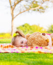 Adorable child resting on backyard in spring time baby girl laying down on green field with teddy bear having fun outdoors happy Stock Images