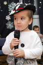 An adorable child years old singing or talking into a microphone cute boy holding on stage dressed as snowman Stock Photo