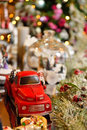 stock image of  Adorable christmas red car toy with santa and presents. Musical miniature decoration on tree bokeh background