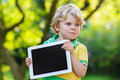 Adorable confused little kid boy holding tablet pc, outdoors Royalty Free Stock Photo