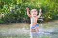 Adorable curly baby girl splashing in river on sunny day a beautiful a Stock Photos
