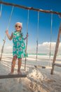 Adorable cute little girl in a dress and sunglasses on swing on white sandy caribbean beach this image has attached release Stock Photo