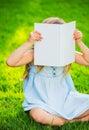Adorable cute little girl reading book in the garden outside on grass Stock Photos