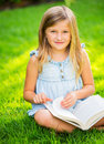 Adorable cute little girl reading book in the garden outside on grass Royalty Free Stock Photo
