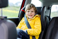 Adorable cute preschool kid boy sitting in car in yellow rain coat. Royalty Free Stock Photo