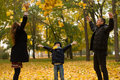 Adorable familly little boy plaing with his mother and father in sunny autumn park Stock Photo