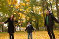 Adorable familly little boy plaing with his mother and father in sunny autumn park Royalty Free Stock Photo