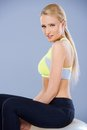 Adorable fitness woman sitting on ball over gray background Royalty Free Stock Photo