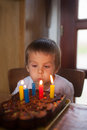 Adorable five year old boy celebrating his birthday and blowing