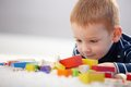 Adorable ginger haired boy playing with cubes little smiling Stock Images
