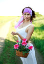 Adorable girl with basket flowers in a field poses Stock Photography