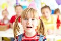 Adorable girl cute in birthday cap looking at camera at party with her friends on background Stock Photos