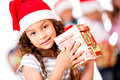 Adorable girl holding a Christmas present Stock Photos