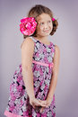 Adorable girl with a pink flower in her hair vertical portrait of an posing studio Stock Images
