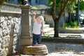 Adorable girl playing with drinking water fountain Royalty Free Stock Photo