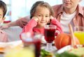 Adorable girl portrait of happy sitting at festive table and looking at camera with her father and brother near by Stock Images