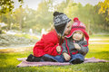 Adorable girl whispers secrets to baby brother outdoors little a secret her wearing winter coats and hats sitting at the park Royalty Free Stock Photography