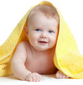 Adorable happy blue-eyed baby in yellow towel Stock Photos
