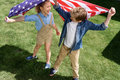 Adorable happy brother and sister waving american flag Royalty Free Stock Photo