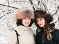 Adorable happy young brunette women girlfriends in fur hats having fun snowy winter park forest in nature Royalty Free Stock Photo