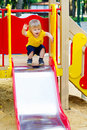 Adorable kid on the playground slide positive little boy is about to go down from Royalty Free Stock Images