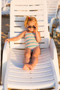 Adorable kid sunbathing on a beach in sunglasses lounge Royalty Free Stock Images