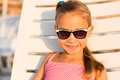 Adorable kid sunbathing on a beach in sunglasses lounge Royalty Free Stock Photos