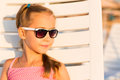 Adorable kid sunbathing on a beach in sunglasses lounge Stock Images