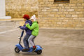 Adorable kids riding electric scooter boy and girl Stock Photo