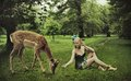 Adorable lady playing with deer Royalty Free Stock Images