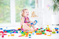 Adorable laughing toddler girl with colorful blocks