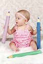 Adorable little baby girl with big crayons Royalty Free Stock Photo