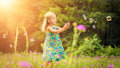 Adorable little blond girl having fun playing with soap bubbles