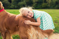Adorable little blond girl hugging her dog Royalty Free Stock Photo