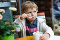 Adorable little boy eating frozen yoghurt ice cream in cafe city Royalty Free Stock Images