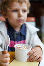 Adorable little boy eating frozen yoghurt ice cream in cafe city selective focus on Stock Photos