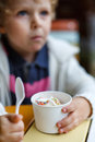 Adorable little boy eating frozen yoghurt ice cream in cafe city selective focus on Stock Photo