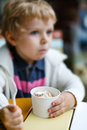 Adorable little boy eating frozen yoghurt ice cream in cafe city selective focus on Royalty Free Stock Photography