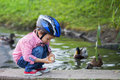 Adorable little boy, feeding ducks Royalty Free Stock Photo