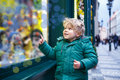Adorable little boy looking through the window at Christmas decoration in the shop Royalty Free Stock Photo