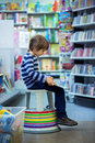Adorable little child, boy, sitting in a book store Royalty Free Stock Photo